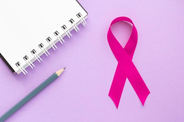 ピンクのリボンと紫色のテーブルのメモ帳、女性の健康の概念、乳がんとの闘い