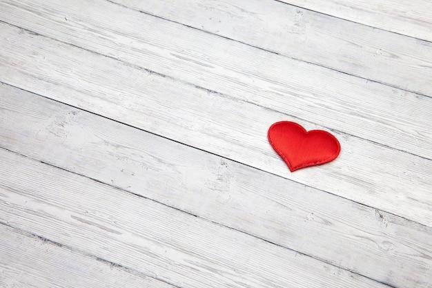 木製の背景、愛の概念、テキスト用のスペースに赤いハート。