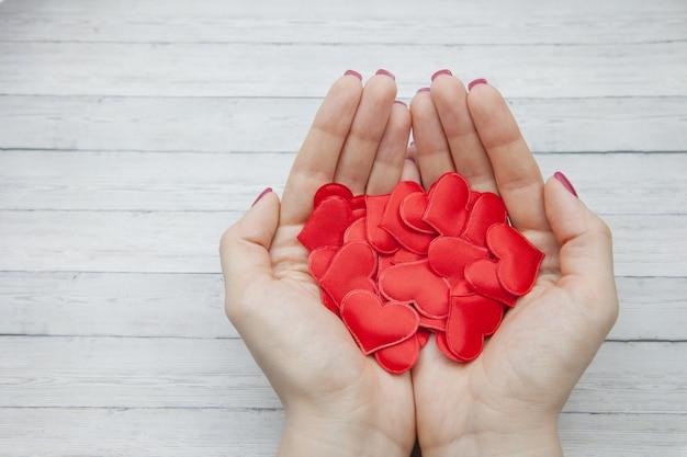 女性の手は、木材の背景、愛を保存するという概念に手のひらに多くの赤いハートを保持します。