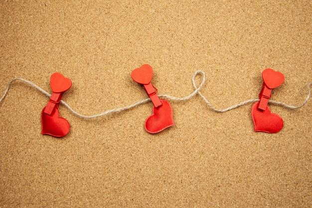 コルクボード、強い愛の概念に洗濯はさみと赤いハート