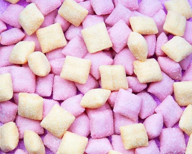 甘いキャンディーパッドピンクの背景にミックスクローズアップ