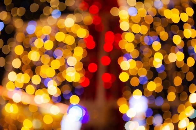 赤と金のきらびやかな輝き電球ライトの抽象的なぼやけた背景