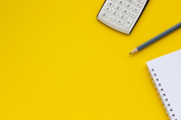 電卓、メモ帳、鉛筆、黄色の背景、テキストのスペース