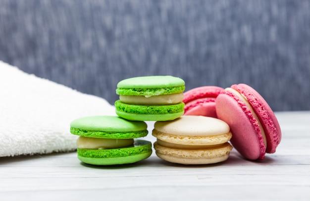 Ассорти красочные миндальное печенье на синем фоне, рядом с белым полотенцем