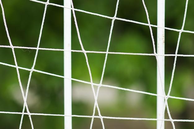サッカー場の鋼格子フェンス、ぼかし背景と金属フェンス。