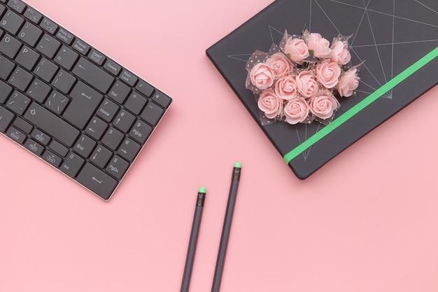 トップビュー、花とピンクの背景にキーボードと鉛筆でノートブック。