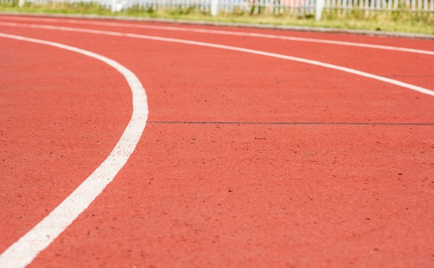 Кривая красная беговая дорожка на стадионе и белая линия на фоне размытия