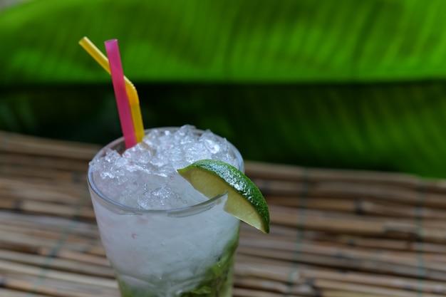 木製の背景のバーで美しいアルコールカクテルライムとミントモヒートドリンク