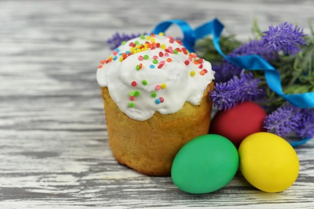 木製の背景に色付きのバスケットに卵とアイシング釉パンとケーキを焼く