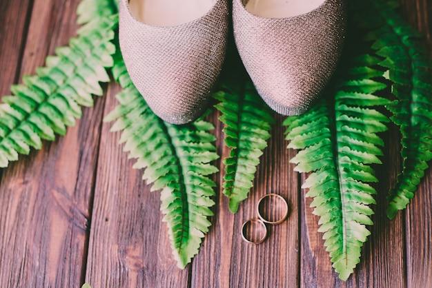 結婚指輪と葉を持つ木製の背景に花嫁の美しい靴