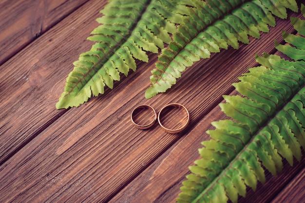 結婚指輪の葉を持つ木製の背景に包まれました。