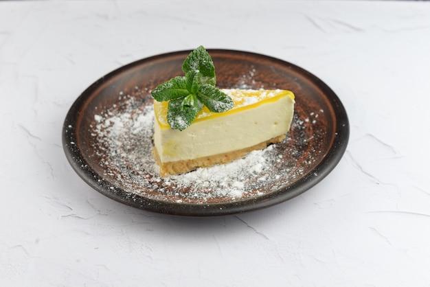白い背景の上のミントの葉とレモンデザートケーキマスカルポーネチーズケーキ