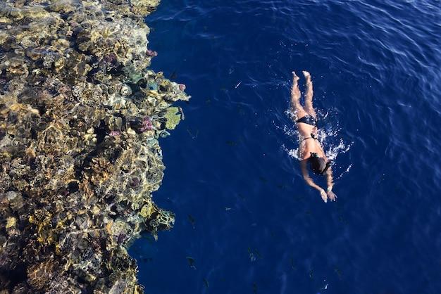 女の子は海でシュノーケリングで泳ぐ