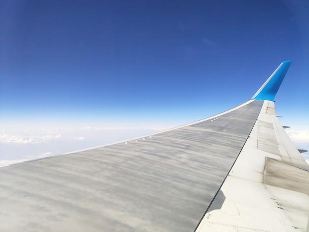 Вид из окна иллюминатора самолета с высоты облала и неба на крыло