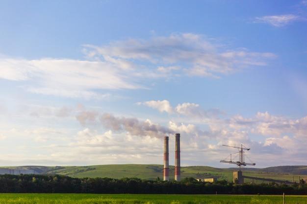 Промышленные трубы с дымом в природе. загрязнение окружающей среды. экологические проблемы.