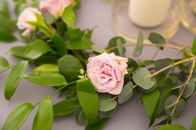 テーブルの上のピンクのバラと美しい枝。結婚式の装飾