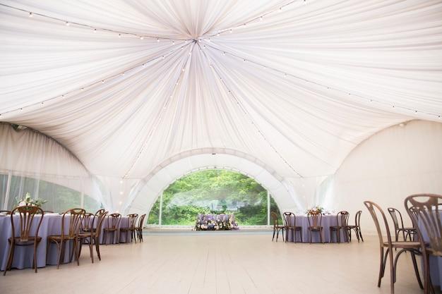 美しい装飾が施された大きな白い結婚式のテント。花飾りと木製の椅子のあるテーブル