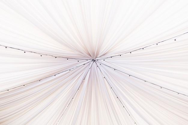 Белая свадебная палатка с декоративными лампочками. интерьер ресторана