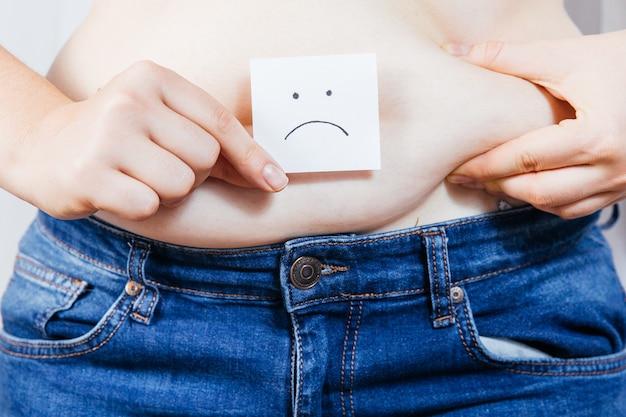 女の子は悲しい顔文字で手で脂肪を保持します
