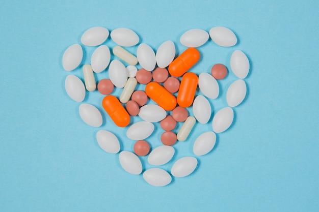 Различные таблетки на синем фоне. здоровье и медицина. сердце