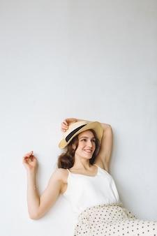 白いシャツと白い背景の上に座っている帽子の若い笑顔の女性