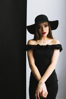 黒のドレスと黒と白の背景に帽子の美しい若い女性