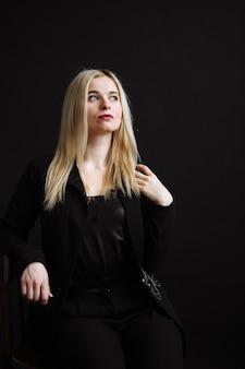 Красивая молодая женщина в черной куртке на черном фоне. белокурая девушка довольно