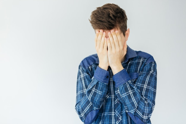 Молодой человек закрывает лицо руками. проблемы и стресс. грустный человек на светло-сером фоне