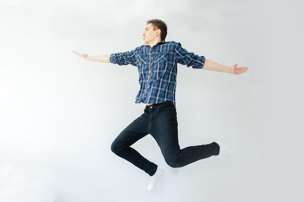 青いシャツと黒いズボンの若い男が明るい灰色の背景にジャンプします。