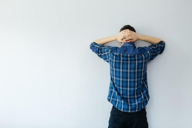 青いシャツを着た若い男が壁に向かっています。うつ病、問題、ストレス