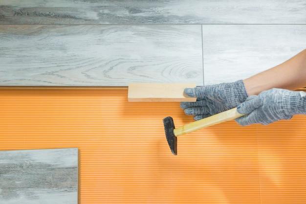 男は新しいラミネートフローリングを置きます。アパートの修理。労働者は床を修理します。ラミネート敷設プロセス