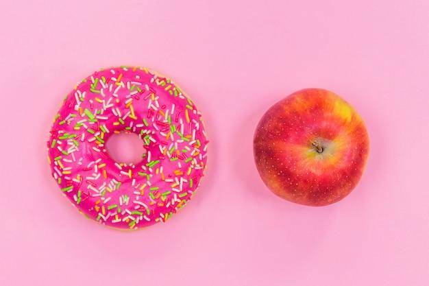 Розовый пончик и яблоко, здоровое питание
