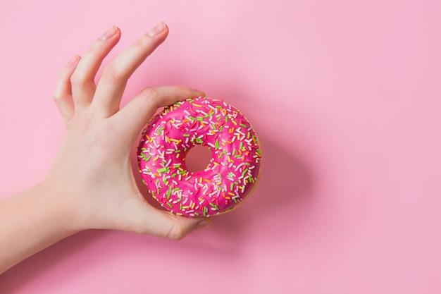 Женщина, держащая розовый пончик на розовом фоне. розовый пончик в руке