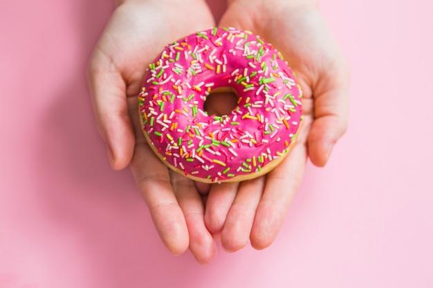 Розовый пончик в руках на розовом фоне. женщина, держащая розовый пончик