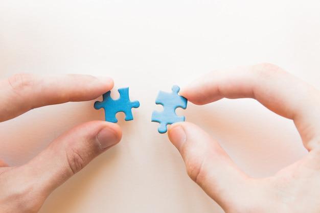 Синяя головоломка в руке. рука головоломки на белом фоне. соединяющий кусочек головоломки, бизнес связь, образование, общество и работа в команде