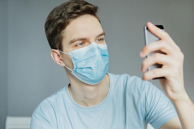 若い男とオンライン接続で話し、手を振って、電話で放送する男性