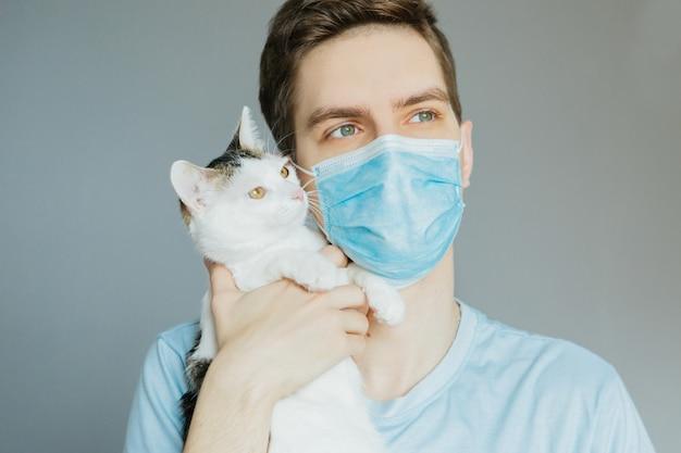 青いシャツと灰色の背景上の手にトラ猫と医療マスクの若い男