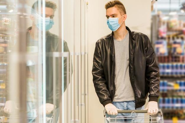 Молодой человек в медицинской маске. карантинная безопасность. человек в магазине