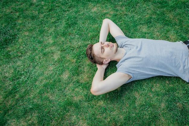 Человек в серой футболке лежа на зеленой траве, лето. отдыхая человек