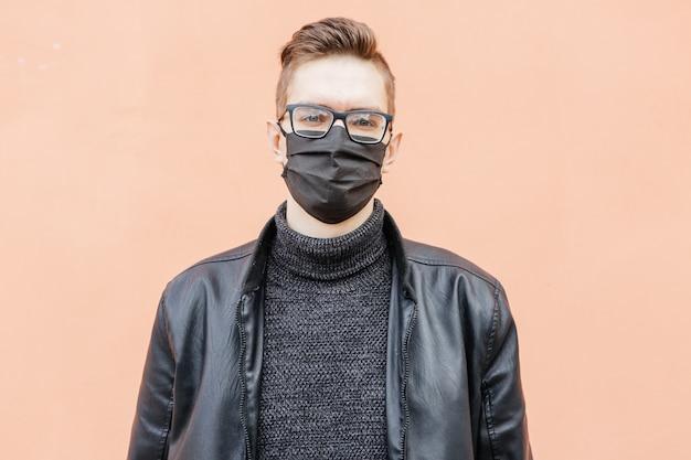Молодой человек в черной медицинской маске и черной куртке, оставаясь на коричневом фоне