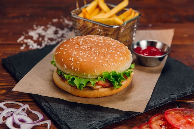 Бургер с картошкой фри и кетчупом на столе в ресторане