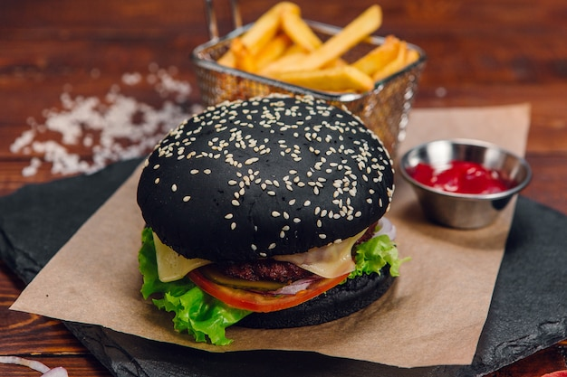 Черный бургер с картофелем фри и кетчупом на столе в ресторане