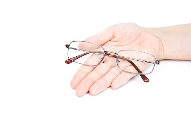 女性の手は、白い背景にグラスを保持しています。手元のメガネ