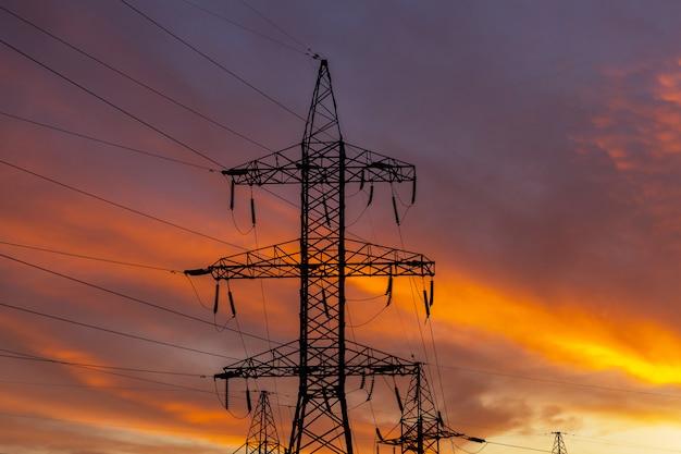 日没時の電力線のシルエット。明るいオレンジの都市の夕日