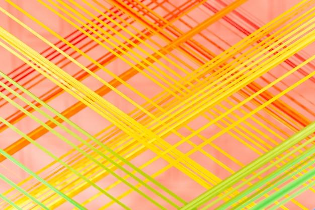 ピンクの背景に黄色とオレンジの繊維ライン。部屋のインテリアの創造的な詳細