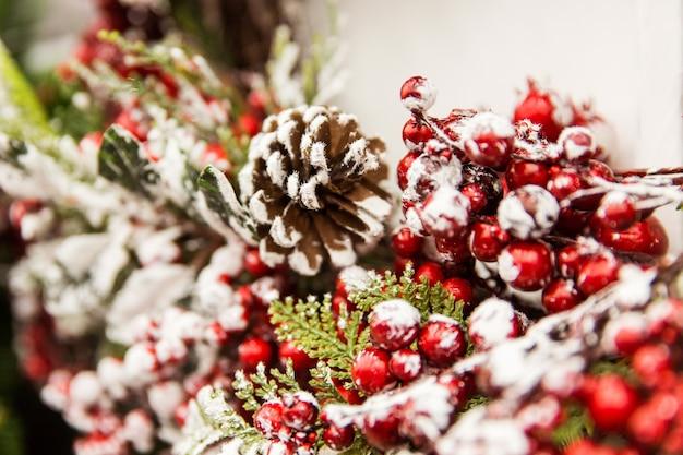 クリスマスの飾り。赤い果実と雪と新年の木の枝