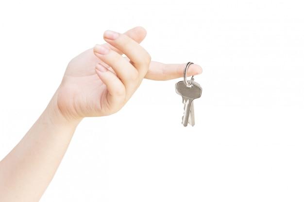 女性の手で金属キー。白い背景に手のキー。白で隔離されて