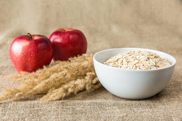 赤いリンゴと繊維の背景にスパイクと白いプレートにオートミール。健康的な食事