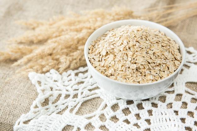 白いボールで、繊維の背景にスパイクとオートミール。健康的な食事