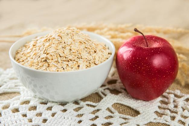 白いボールのオートミール、繊維の背景に赤いリンゴ。健康的な食事